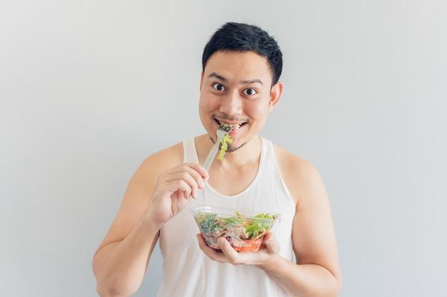 幸せな男は健康的なサラダの食事を食べています。