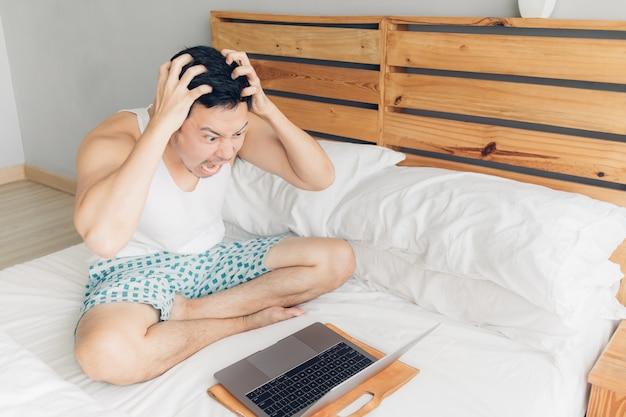 怒っている人は彼のベッドの上の彼のラップトップで働いています。