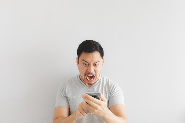 Злой человек в серой футболке злиться на смартфоне.