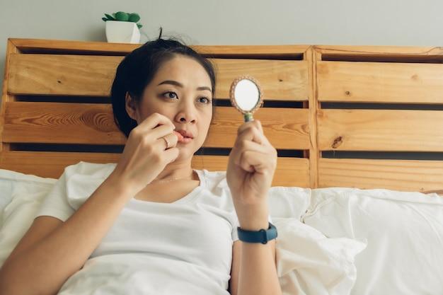 女性は寝室のベッドで化粧をしています。