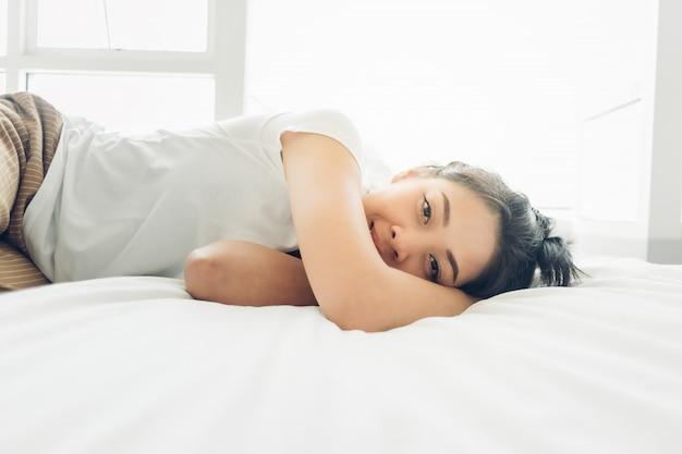 アジアの女性は彼女の白い居心地の良いベッドで寝ています。