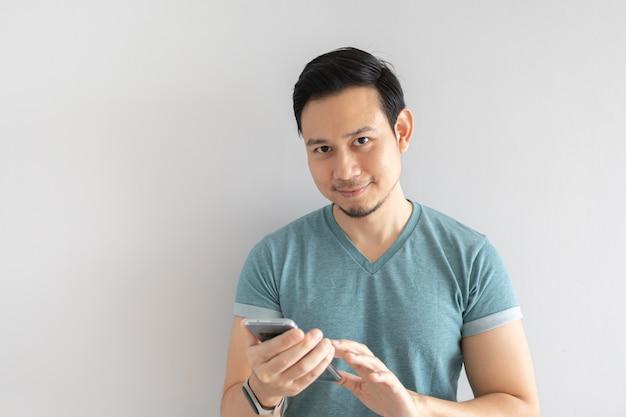 幸せな男は彼のスマートフォンを使用しています。
