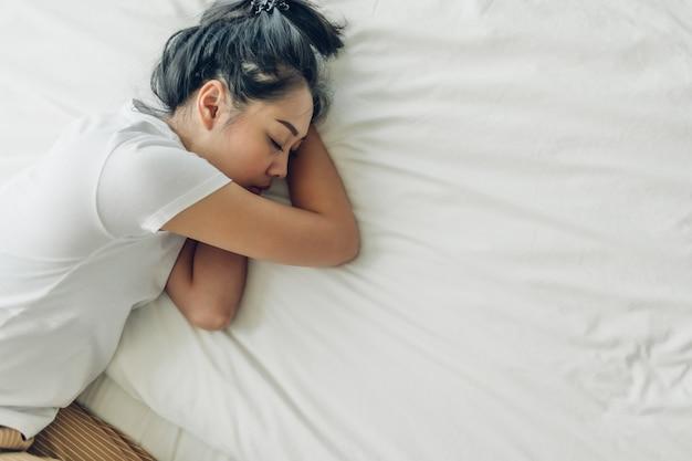Взгляд сверху женщины спать на ее кровати с белым космосом экземпляра.