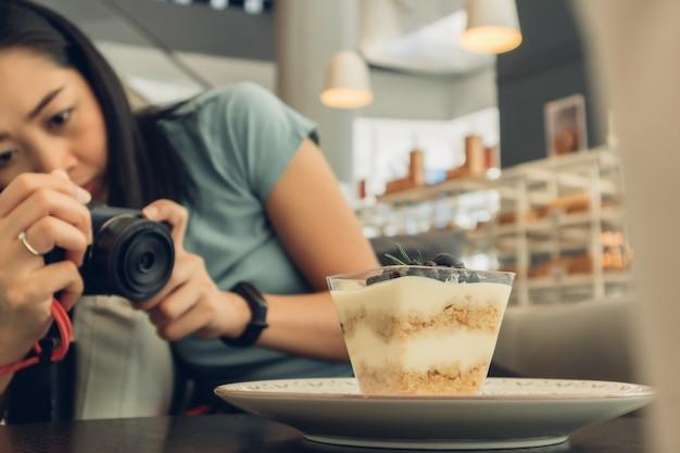 Женщина берет фотографию ее черничный чизкейк.