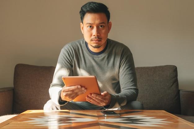 男は彼のリビングルームのアパートで彼のスマートタブレットデバイスを使用しています。