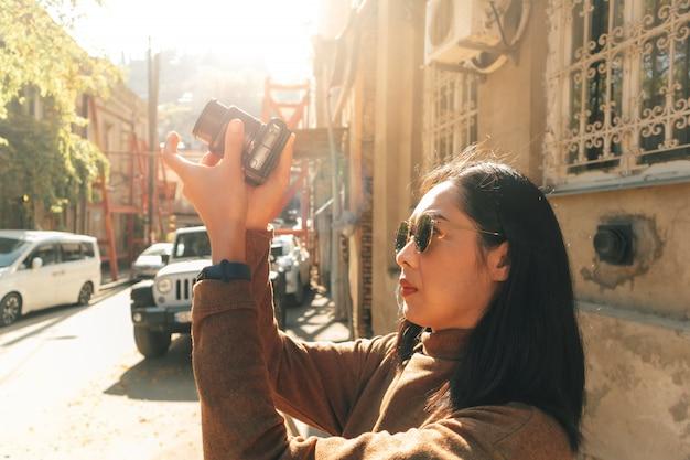 女性観光客は、ヨーロッパの町で写真を撮っています。
