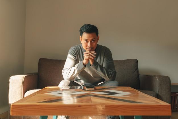 男は彼のリビングルームのソファに座って、朝はリラックスした感じ。