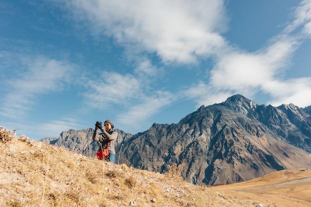 女性観光客が山の風景の写真を撮っています。