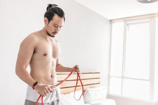 抵抗バンドと自宅でのトレーニングの概念で彼の筋肉を伸ばす男。