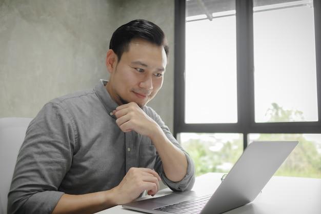 Счастливое лицо человека, работающего на ноутбуке только в комнате.