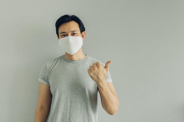 Нормальное лицо человека в белой гигиенической маске в серой футболке с копией пространства.