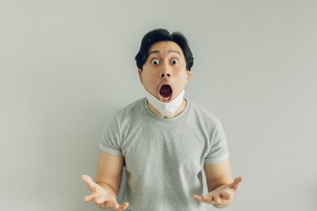 Шокирован и удивлен лицо человека в белой гигиенической маске в серой футболке.
