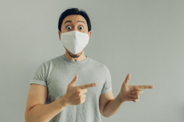 Ничего себе лицо человека в гигиенической маске и серой футболке.