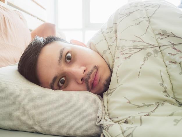 Азиатский мужчина не может спать на утреннем свете с бессонными черными глазами.