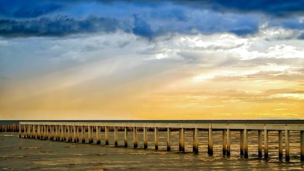 夕日と橋の間の海の上の雨と嵐の雲は、海に広がる