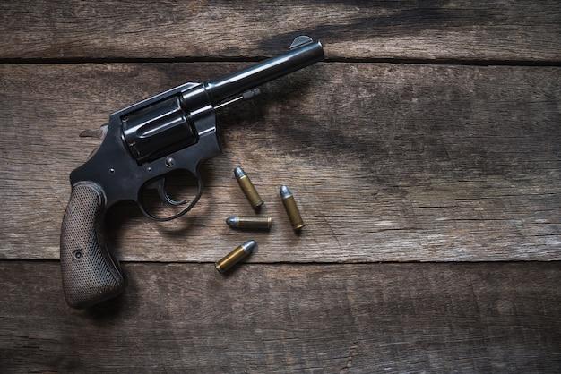 Оружие и боеприпасы на деревянном столе. вид сверху