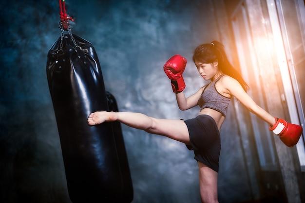 セクシーなアジアの女の子がボクシングバッグをパンチ
