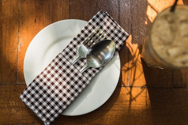 クローズアップスプーンとの上の木製テーブル