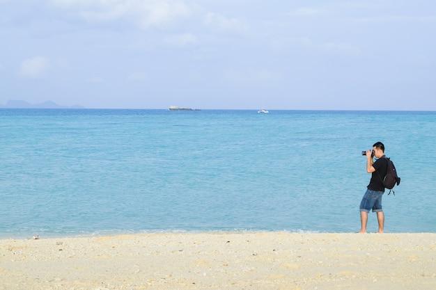 写真家は海で写真を撮る
