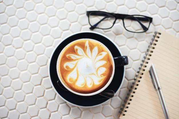 白いテーブル上のコーヒーのラテアートカップ