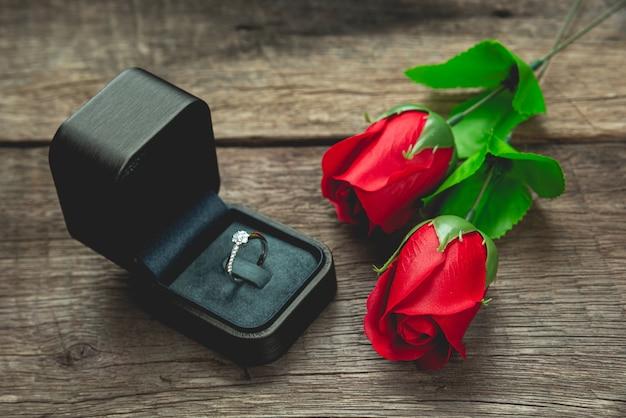 結婚指輪と木製のテーブルに赤いバラの花