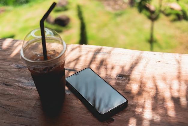 木製のテーブルに置かれた携帯電話とアイスコーヒー