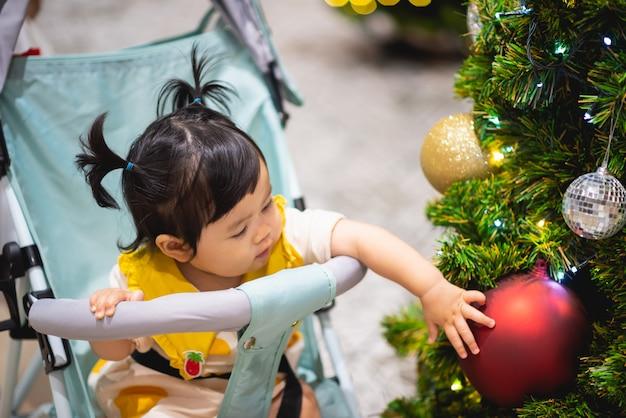 Младенец играя с рождественским шаром и сосной
