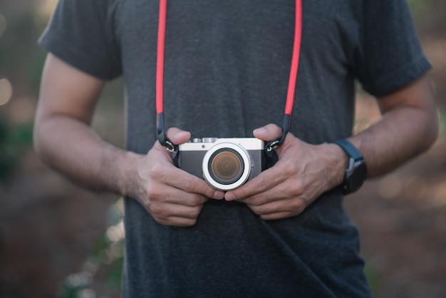 写真を撮るためにカメラを持って写真家のクローズアップ