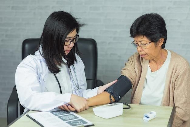 Доктор проверяет давление старуха на сером