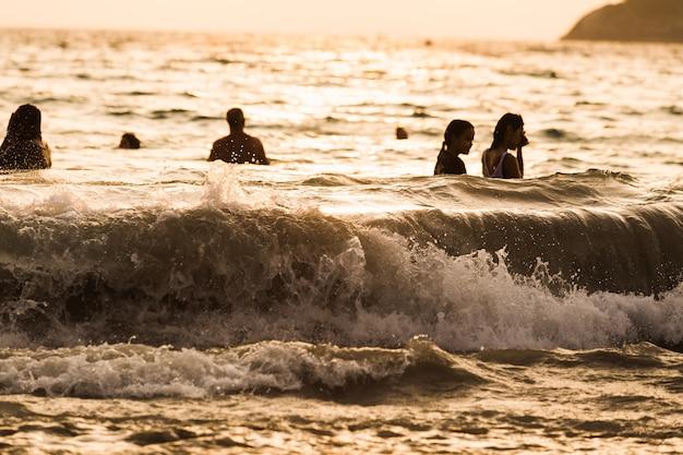 シルエットの人々波海のビーチの夕日