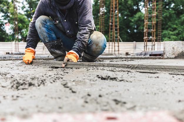 工具コンクリートを使用した産業建設の男性労働者