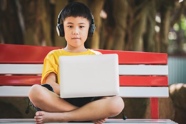 アジアの少年の笑顔顔を立て、音楽を聴く