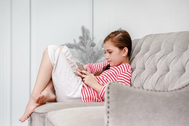Маленькая девочка, сидя на диване, играет в смартфон в гостиной