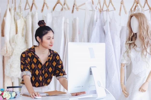 Азиатский дизайнер, работающий в магазине свадебной моды