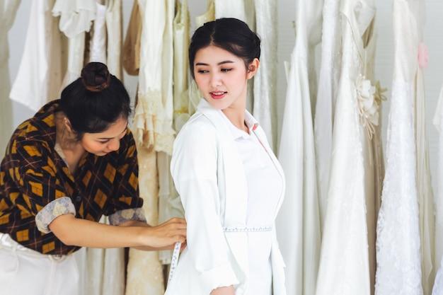 Азиатский дизайнер работает в магазине свадебной моды
