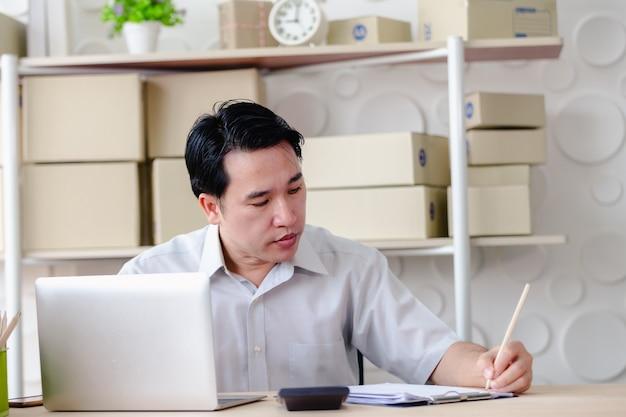 中小企業の中小企業、男性は非常に満足して作業を探してオンラインノートパソコンで