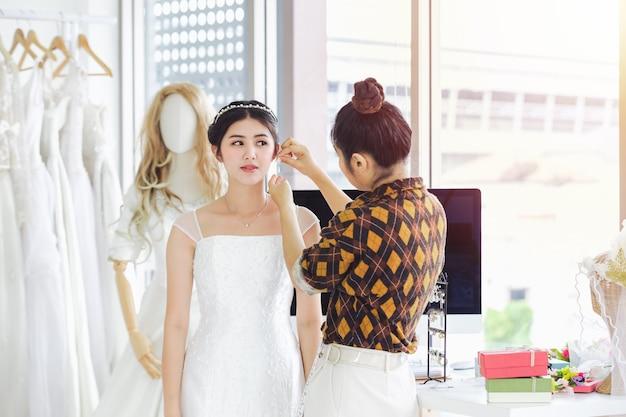 アジアのデザイナーの結婚式のファッション店で働いて