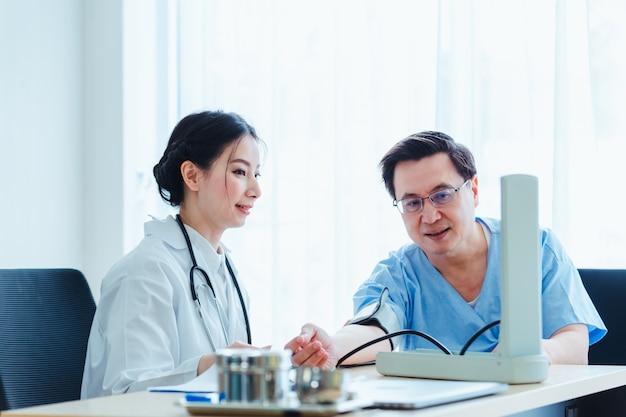 医者の女性が診療所で医療と話している患者男性で血を測定