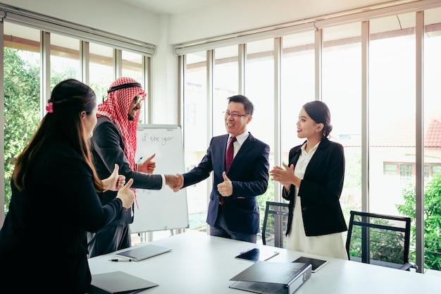 ビジネス会議のアジアチームと事務室で彼のアイデアを提示するアラビア人