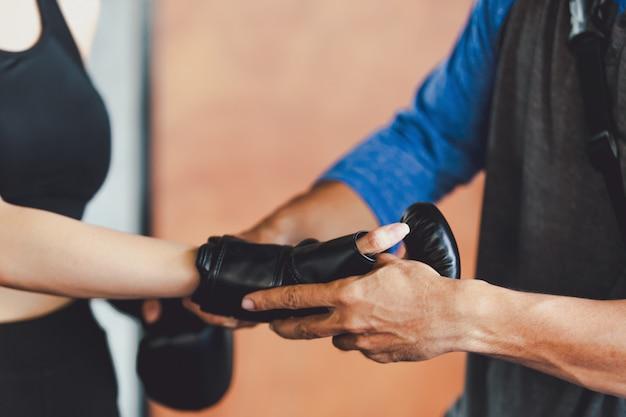 スポーティな女の子ジムでトレーニングボクシンググローブを持つ美しい女性