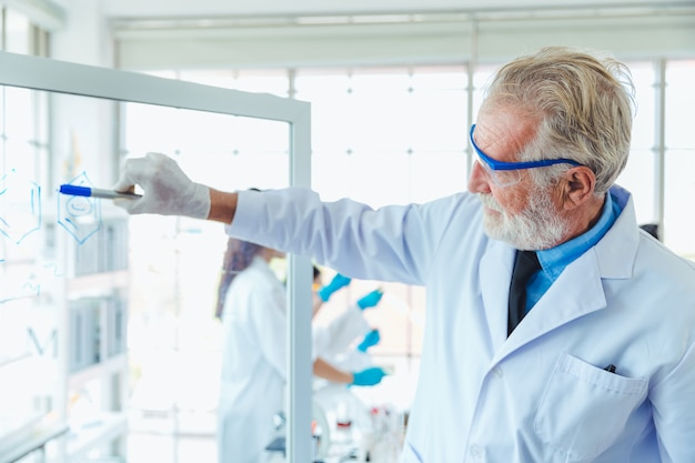 研究室で透明なガラス板化学物質を扱う科学教師男性