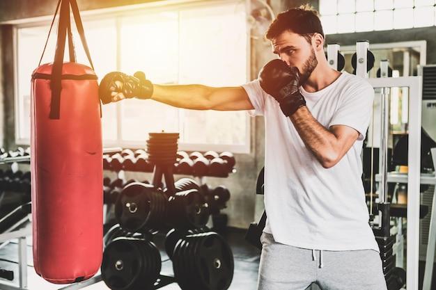 バックボクシンググローブ、ジムでトレーニングを持つスポーティな男性の肖像画