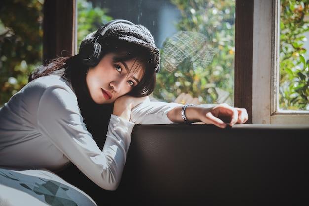 Эмоции чувствуя молодая девушка грустно слушать музыку, глядя в окно