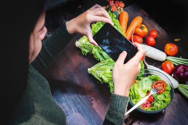 アジアの美しい若い女の子のサラダ野菜を食べる