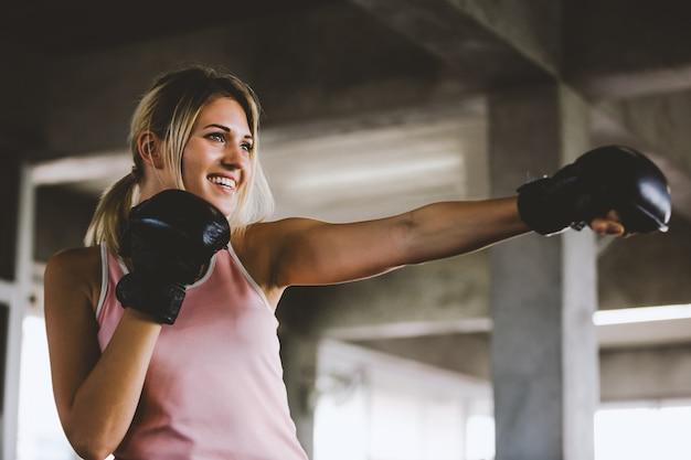 スポーティな女の子の肖像画、ジムでトレーニングボクシンググローブを持つ美しい女性