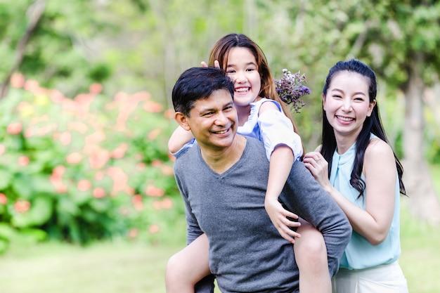 Веселая семья, пикник вместе отдохнуть на зеленой природе в парке