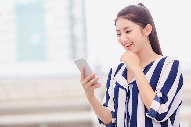 Молодая женщина на открытом воздухе образ жизни, глядя на смартфон
