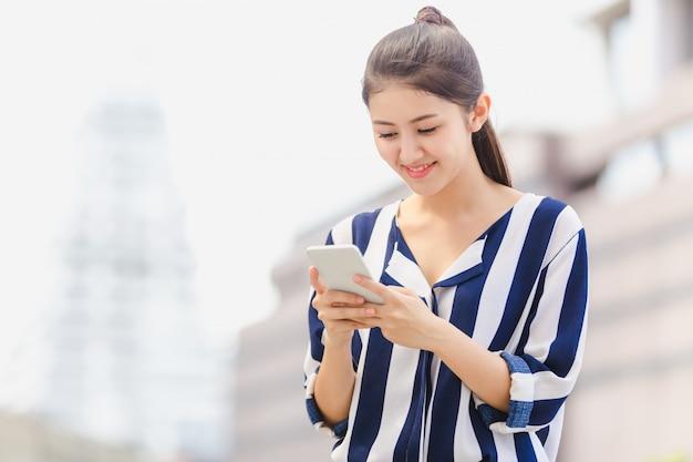 スマートフォンを探している屋外のライフスタイルの若い女性