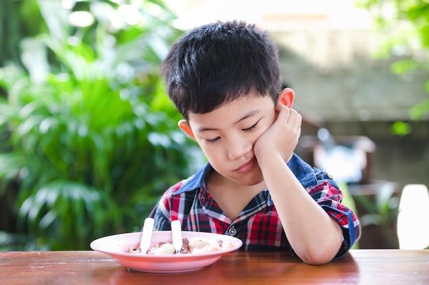 アジアの少年は、米の食べ物を食べて退屈