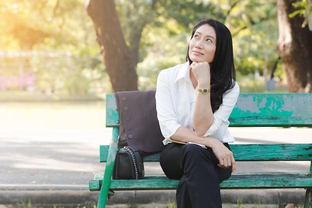 公園でアジアの美しいビジネス女性のリラクゼーション